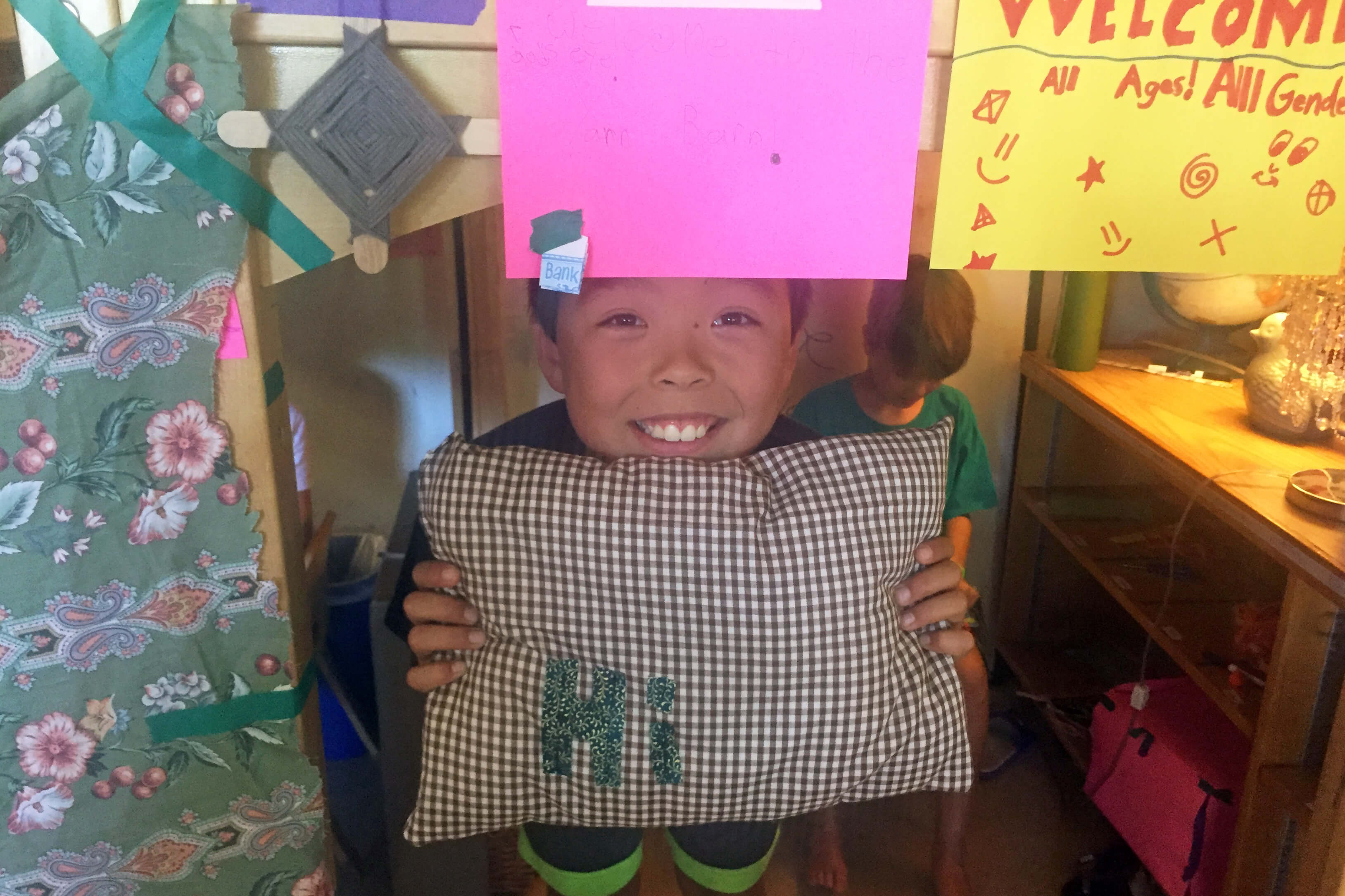A young boy smiles while holding a pillow he created that says hi
